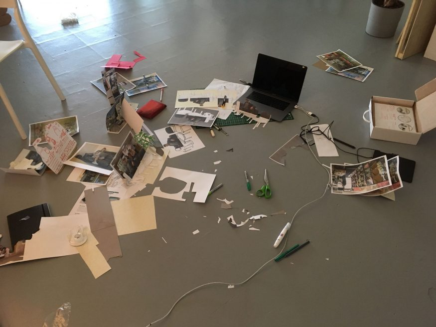 A laptop, cutting mat, several exacto knives, cut-out paper, jar of pens, and scraps of paper, spread messily around a concrete floor.