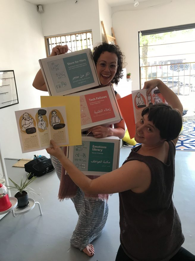 Alysha and Melanie juggling several labeled boxed and some of the contents from within, to show them off
