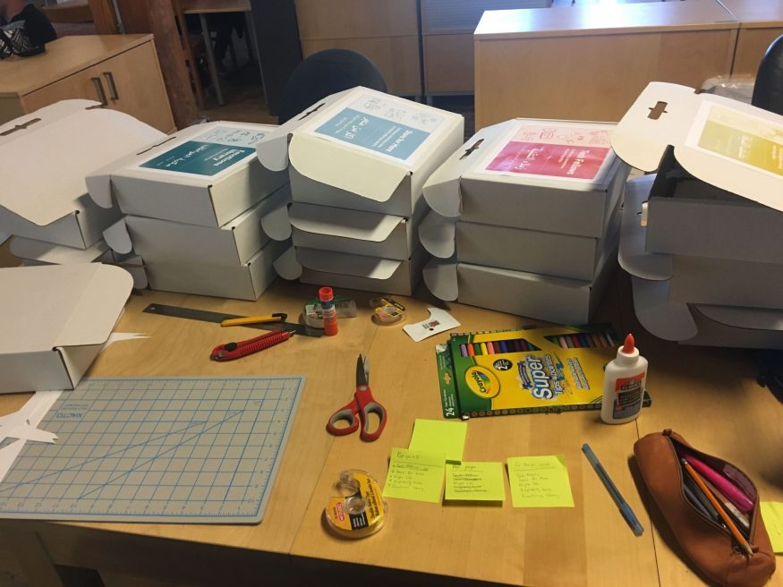 Boxes piles high on a desk strewn with glue, scissors, ruler, self-healing mat, tape, and felts.
