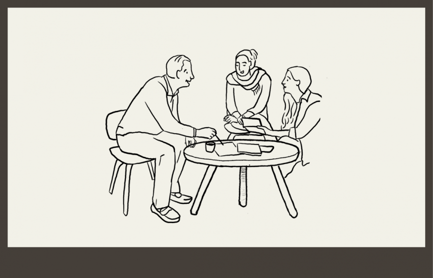 Three people sitting around a table discussing