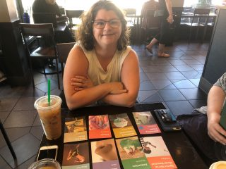 An end user smiles proudly with arms crossed over her chest, leaning on a cafe table that contains a grid of colourful cards with various titles and a frozen coffee drink.
