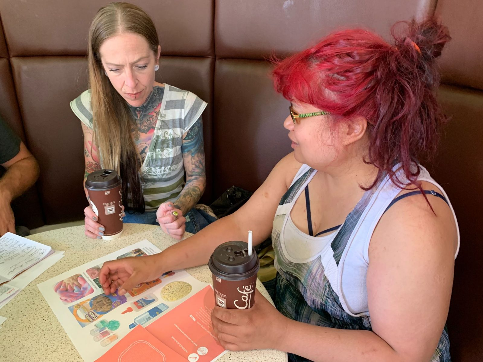 Two women sitting in a booth, one with long, straight blond hair, tattoos on her exposed neck, collar bone, and upper arms. The other has dyed bright red hair, and is wearing overalls. Both are holding a paper McDonald's coffee cup in their hands, resting on the table. They are looking down at colourful paper materials.